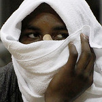 San Antonio Spurs' DeJuan Blair wraps a towel around his head as he watches from the bench in the second half of the NBA preseason basketball game against the Cleveland Cavaliers on the Univ ...