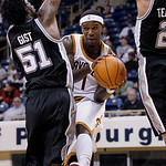 Cleveland Cavaliers' Daniel Gibson, center, passes between San Antonio Spurs' James Gist, left, and Garrett Temple in the second half of the NBA preseason basketball game on the University o ...
