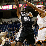 San Antonio Spurs' James Gist, left, goes over Cleveland Cavaliers' Samardo Samuels to score in the first half of the NBA preseason basketball game on the University of Pittsburgh campus, Th ...
