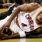 Cleveland Cavaliers' Atawn Jamison grabs his knee after tumbling over San Antonio Spurs' James Gist in the first half of the NBA preseason basketball game on the University of Pittsburgh cam ...