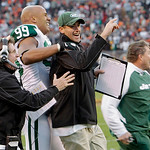 New York Jets linebacker Jason Taylor (99) celebrates with assistant head coach Bill Callahan, left, and an unidentified staff member after a 26-20 overtime win over the Cleveland Browns in  ...