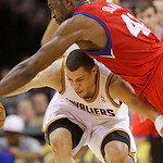 Cleveland Cavaliers guard Anthony Parker tries to get past Philadelphia 76ers forward Elton Brand, top, in the third quarter in an NBA basketball game Tuesday, Nov. 16, 2010, in Cleveland. T ...