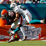 Cleveland Browns cornerback Joe Haden, left, intercepts a pass intended for Miami Dolphins wide receiver Brian Hartline (82) in the second quarter during an NFL football game in Miami, Sunda ...
