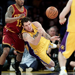 Los Angeles Lakers forward Luke Walton, center, passes the ball to Steve Blake as he is defended by Cleveland Cavaliers guard Alonzo Gee during the first half of an NBA basketball game in Lo ...