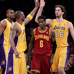 Cleveland Cavaliers guard Manny Harris, center, walks down the court as Los Angeles Lakers forward Pau Gasol, right, of Spain, is greeted by Kobe Bryant after Gasol made a basket during the  ...
