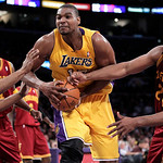 Los Angeles Lakers center Andrew Bynum, center, is defended by Cleveland Cavaliers shooting guard Alonzo Gee, left, and Samardo Samuels during the second half of an NBA basketball game in Lo ...