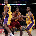 Los Angeles Lakers guard Kobe Bryant, right, attempts to steal the ball from Cleveland Cavaliers forward Samardo Samuels, center, during the first half of an NBA basketball game in Los Angel ...