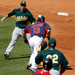 Cleveland Indians' Asdrubal Cabrera escapes a run down between Oakland Athletics left fielder Chris Carter, bottom, and short stop Eric Sogard during the fourth inning of a spring training b ...