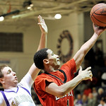 Mike Cannon, right, of Elyria drives to the basket while defended by Vermilion's Cameron Zima last night. DAVID RICHARD / CHRONICLE