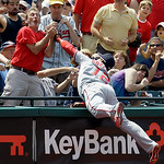 Washington Nationals third baseman Alberto Gonzalez (12) and a fan try to catch a pop foul by Cleveland Indians' Russell Branyon in the sixth inning of a baseball game in Cleveland on Sunday ...