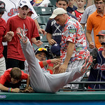 Washington Nationals third baseman Alberto Gonzalez, center, tumbles into the crowd while trying to catch a pop foul by Cleveland Indians batter Travis Hafner in the ninth inning of a baseba ...