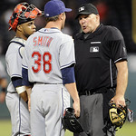 Cleveland Indians pitcher Joe Smith and  catcher Carlos Santana argue with home plate umpire Bob Davidson that Texas Rangers' Nelson Cruz's home run was foul in the seventh inning of a baseb ...