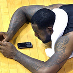 LeBron James works on one of his BlackBerry devices after the evening workout games with high school basketball players at his skills academy, Tuesday, July 6, 2010, in Akron, Ohio. (AP Phot ...