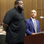 Cleveland Browns defensive lineman Shaun Rogers appears in Cuyahoga County Common Pleas Court with his attorney Pat D'Angelo during his arraignment on carrying a concealed weapon charge in C ...