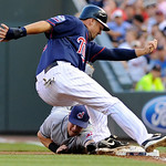 Cleveland Indians first baseman Matt LaPorta, bottom, reaches in vain on his tag attempt as Minnesota Twins' Michael Cuddyer returns safely to first base after Delmon Young flew out to deep  ...