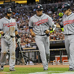 Cleveland Indians' Carlos Santana, left, and Jhonny Peralta, center, score on a single by Shelley Duncan as on-deck batter Trevor Crowe, right, welcomes them in the sixth inning of a basebal ...