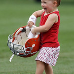 Elle Ratliff, 2, daughter of Cleveland Browns quarterback Brett Ratliff, delights in carrying her father's helmet from the playing field following the Browns NFL football training camp, in B ...