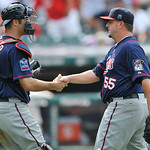 Minnesota Twins pitcher Matt Capps, right, shakes hands with catcher Joe Mauer after earning a save in a 5-4 win over the Cleveland Indians in a baseball game in Cleveland, Sunday, Aug. 8, 2 ...