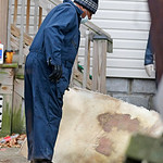 An investigator looks at carpeting that came from Anthony Sowell's home Wednesday, Nov. 18, 2009, in Cleveland. Investigators looking into the discovery of 10 bodies and a skull at the home  …