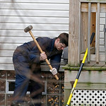An investigator uses a sledgehammer to break a concrete slab under the back porch at the home of Anthony Sowell Wednesday, Nov. 18, 2009, in Cleveland. Investigators looking into the discove …