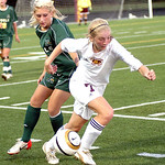 Avon Lake&#039;s #7 Claire Jones takes the ball past Amherst&#039;s #5 Emily Varouh.