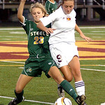 Amherst's #23 Gabby Semon fights Avon Lake's #9 Claire Adams for the ball.