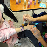 Eyla French, 4, of Avon, has a hand painting done by Kathy Domlin at the Avon Lake Homecoming Festival Oct. 2.   Steve Manheim