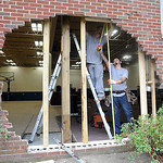 Tom Tomlinson, left, and Adam Vasi, of Platiunum Restoration in Elyria, board up the gym wall where a car crashed  at the Boys and Girls CLubs of Lorain County in Elyria on Wed. morning Jul  …