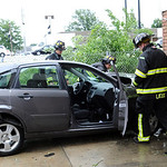 Elyria firefighters look over a car which ran into Wolfey's on E. Broad St. after a collision on Rt. 57 on June 1.   Steve Manheim
