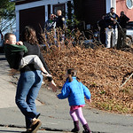 A mother runs with her children as police above canvass homes in the area following a shooting at the Sandy Hook Elementary School in Newtown, Conn., about 60 miles (96 kilometers) northeast …