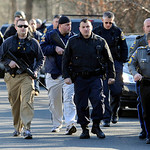 Law enforcement canvass the area following a shooting at the Sandy Hook Elementary School in Newtown, Conn., about 60 miles (96 kilometers) northeast of New York City, Friday, Dec. 14, 2012. …