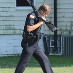 Lorain County sheriff moves a rifle to from a squad car to another car on July 15 shooting at W River Rd home.   Steve Manheim