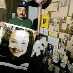 FILE – In this Friday, March 3, 2004 file photos shows Felix DeJesus, holding a banner showing his daughter's photograph, standing by a memorial in his living room in Cleveland. Cleveland po …