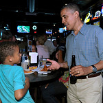 President Barack Obama talks with child at Ziggy's Pub and Restaurant in Amherst, Ohio, Thursday, July 5, 2012. Obama is on a two-day bus trip through Ohio and Pennsylvania. (AP Photo/Susan …