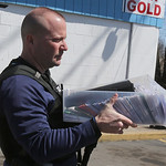 An Elyria Police Officer carries a plastic tub loaded with hundreds of individually packaged DVDs. This was just one of several boxes taken from the Shopway Food mart on Lake Avenue in Elyri …