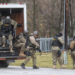 SWAT team members jump out of their vehicle as they head towards the house on Route 303 in Pittsfield Township where a man held them at bay for most of the day. Officers found him dead of a …
