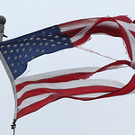 The flag outside the Sheffield Lake Community Center on Lake Road shows the wear and tear from the storm.