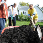 Alicia Bosma, left, of Carlisle Twp., Allison Brown-Smith, of United Way of Greater Lorain County, and Leon Bibb of NewsChannel 5,  move mulch at a home on S. Maple St. in Elyria for Buildin …