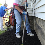 Rachel Speidel, of Elyria Charities, rakes out mulch at a home on S. Maple St. for Builiding Better Communities on Sep. 28.   Steve Manheim
