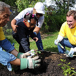 Leon Bibb, left, and Chris Flanagan, of NewsChannel 5, plant flowers with the help of Alaila Davis, 3, of Elyria, and her grandmother,  Councilwoman Brenda Davis, 2nd Ward, at a community ga …