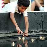 Malik Holt, 11, of Elyria, places candles in the fountain at Ely Square for the 11th anniversary 9/11 Candlelight Service at Ely Square on Sep. 11, 2012.   Steve Manheim