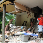 In this Oct. 5, 2010 photo, Jay Snyder carries his nephew Gavin while helping retrieve some of his brother's property after a car crashed into the home in Massieville, Ohio. (AP Photo/Chilli …