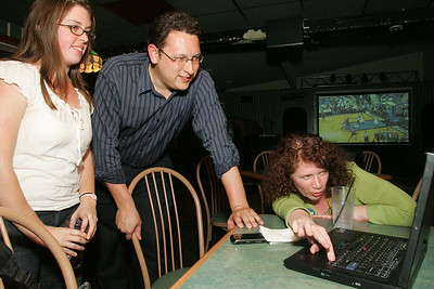"""Erin Sync, left, a supporter and volunteer with the Dan Ramos (center) campaign, and supporter Cheri Campbell view figures a Mutt & Jeff's in Lorain. Ramos was """"cautiously optimistic"""" for a turn around in those early figures, but it was not to be.  photo by Chuck Humel"""
