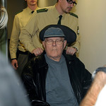 Police officers and medical assistants escort defendant John Demjanjuk, who sits in a wheel chair, during a trial break in the country court in Munich, southern Germany, on Monday, Nov. 30, …