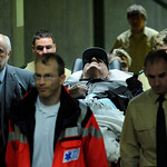 Police officers and medical assistants escort the defendant John Demjanjuk, who lies on a stretcher, prior to the second day of his trial in the country court in Munich, southern Germany, on …