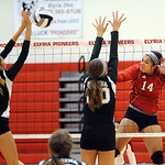 Elyria 14 Kayla Young hits past Medina 3 Leah Svoboda, left, and Kelly Kaletta at Elyria on Sep. 6.  Steve Manheim