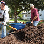 John Fath, left, of Gates Ave. in Elyria, and Tom Lahetta, pres. of North Coast Building Industry Association, move mulch on Gates Ave. for Building better communities on Sep. 28.   Steve Ma …