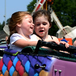 New friends Grace Johnson, 4, of Lakewood, and Reese Ehler, 2, of Columbus, ride the Dragon Ride on Saturday.  KRISTIN BAUER | CHRONICLE