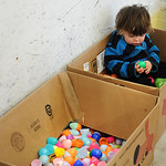 After participating in the 'under-2' Easter Egg Hunt, Jack Ternes, 2, of Lorain, relaxes in one of the large plastic egg recycling bins as he removes the candy from his eggs. KRISTIN BAU …