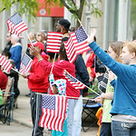 People line the sidewalk along Broad Street waving American flags as they watch the annual Elyria Memorial Day Parade yesterday morning in downtown Elyria. (CT photo by Anna Norris.)